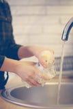 Pratos de secagem da mulher na cozinha Imagem de Stock