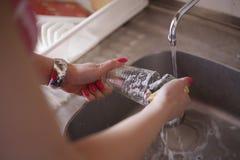 Pratos de secagem da mulher na cozinha fotografia de stock
