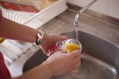 Pratos de secagem da mulher na cozinha imagens de stock royalty free