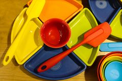 Pratos de serviço e plasticware brilhantemente coloridos - vista superior na superfície de madeira foto de stock royalty free