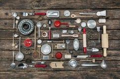 Pratos e cutelaria velhos em um fundo de madeira no vermelho, prata e Imagens de Stock