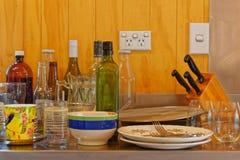Pratos e garrafas desordenados em uma banca da cozinha de aço inoxidável imagens de stock