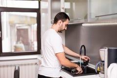 Pratos estando e de lavagem do homem novo feliz na cozinha imagens de stock royalty free