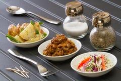 Pratos laterais do BBQ na tabela preta com forquilha, colher, sal, pimenta e palitos fotografia de stock royalty free