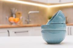 Pratos limpos da porcelana azul em uma tabela branca de madeira foto de stock