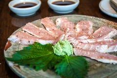 Pratos mouthwatering do restaurante japonês, carne de porco fresca decorada com flores fotos de stock royalty free