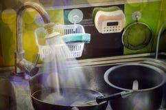 Pratos sujos nos potenciômetros e nos utensílios de mesa do dissipador prontos para lavar Imagens de Stock