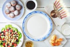 Pratos tradicionais do Hanukkah na opinião de tampo da mesa de madeira branca imagem de stock royalty free
