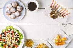 Pratos tradicionais do Hanukkah na tabela de madeira branca foto de stock