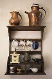 Pratos velhos Cookware histórico Velho hunged na prateleira de madeira na parede medieval Fotos de Stock Royalty Free