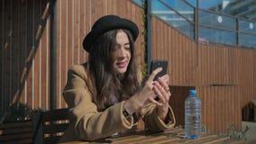 Pratsam flicka på tabellen med en smartphone stock video