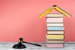 Prawa pojęcia otwarta książka z drewnianym sędziego młoteczkiem na stole w sala sądowej egzekwowania prawa biurze lub, różowy tło Obraz Stock