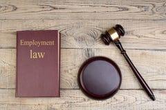 Prawa pojęcie - Zatrudnieniowy prawo Otwiera prawo książkę z drewnianym sędziego młoteczkiem na stole w egzekwowanie prawa biurze fotografia royalty free