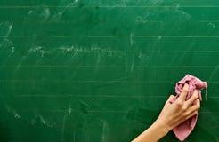 Prawa ręka młoda dziewczyna czyści zielonego zarządu szkoły z różowym ręcznikiem fotografia royalty free