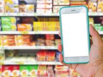 Prawa ręka mienie zieleni pustego ekranu telefon komórkowy z supermar Obrazy Royalty Free