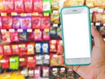 Prawa ręka mienie zieleni pustego ekranu telefon komórkowy z supermar Obraz Stock