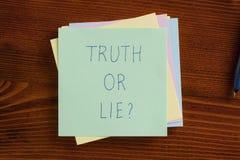 Prawda lub kłamstwo pisać na notatce fotografia royalty free