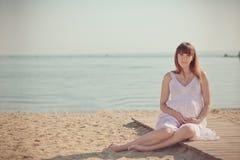 Prawdziwa śliczna ciężarna damy kobieta w białej powiewnej smokingowej siedzącej piasek plaży palety mosta mienia brzuszka drewni zdjęcia stock
