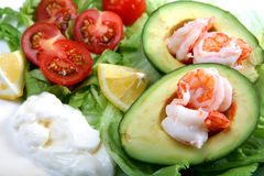Prawn avacado boats. Prawns (or shrimps) in avacado (or guacamole) boats, with a lettuce and tomato salad, mayonnaise and lemon wedges Stock Photos