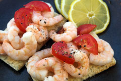 Prawn-breads. Prawns & black pepper on crisp-bread with tomatoes Royalty Free Stock Photography