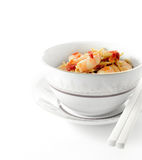 Prawn Noodles. Fresh Chinese noodles with stir fried Tiger prawns in ceramic bowl and chop sticks against a white background. Copy space stock photos