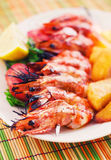 Prawn skewer with a side of baked potatoes Royalty Free Stock Image