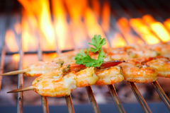 Prawn spit on grill. Delicious prawn spit on grill with flames in background Royalty Free Stock Photography
