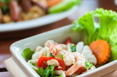 Prawn and squid spicy salad on dish wood background, Thai traditional mix seafood stock image