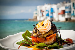 Prawn starter on the sea. Prawn starter with aubergine, tomato and salad by the sea in Mykonos, Greece Stock Photos