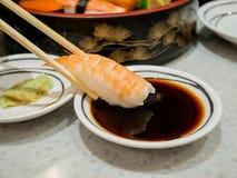 Prawn sushi in chopsticks Royalty Free Stock Photos