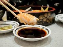 Prawn sushi in chopsticks Royalty Free Stock Photography