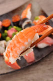Prawn sushi held by chopsticks Royalty Free Stock Photos
