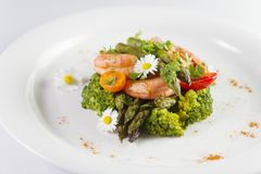 Prawns, asparagus and broccoli with edible daisy flowers Royalty Free Stock Photography