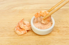Prawns and dip. Prawn in chopsticks dipping in seafood sauce with two prawns on a wooden board Stock Photos