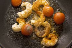 Prawns grilling with tomato and chili spice Stock Photo