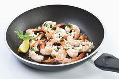 Prawns with lemon slices in frying pan. Stock Image