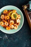 Prawns roasted on grill and boiled brown rice on plate. Grilled shrimps, prawns with rice. Seafood. Asian cuisine. Top view. Dark background stock photography