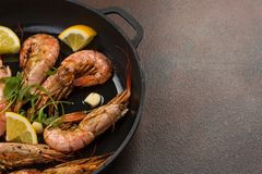 Prawns shrimps with garlic, lemon, spices and italian parsley garnish in a black pan on white painted rustic wood, selected focus, stock image