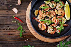 Prawns Shrimps roasted in garlic butter with lemon and parsley. On wooden background. Healthy food. Top view. Flat lay stock images
