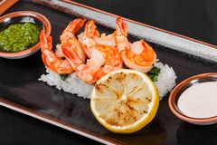 Prawns Shrimps roasted with sauce, greens and rice on black plate on wooden background. Delicious dish of seafood. Japanese cuisine. Top view royalty free stock images