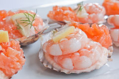 Prawns And Smoked Salmon. In scallop shells garnished with dill and lemon Royalty Free Stock Photography