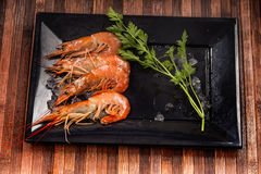 Prawns and vegetable on a black plate Royalty Free Stock Images