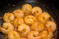 Prawns in a wok. Sizzling prawns in a wok with garlic and chilli sauce royalty free stock photography