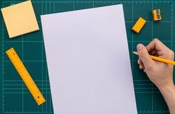 Praworęczny z ołówkiem przygotowywa pisać w papierze na rozcięcie macie obraz royalty free