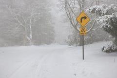 Prawy zwrota znak ostrzegawczy na zimy drodze Obraz Royalty Free
