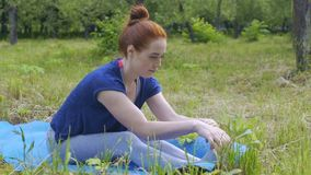 Praxis der jungen Frau, die draußen, weiblich im Park tut Yoga auf Matte ausdehnt stock video footage