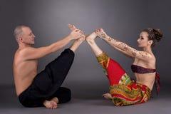 Praxisyoga in den Paaren Bild auf grauem Hintergrund Lizenzfreie Stockfotos