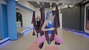 Praxisyoga mit zwei Frauen in den Hängematten im Studio stock video