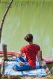 Praxisyoga-Sommertag des jungen Mannes durch das Seepositionsverdrehen des vollen Körperschusses des Dorns stockfoto