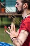 Praxisyoga-Sommertag des jungen Mannes durch die Seehände in Grußnamaste Position auf Herz chakra stockfotografie